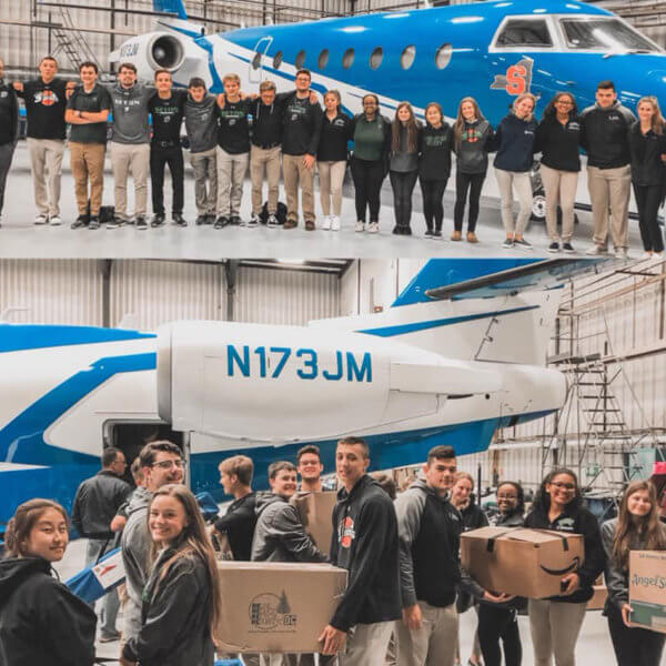 A group of students packing boxes in front of Adam Weitsman's private jet